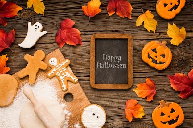 Maqueta con golosinas de halloween y hojas de otoño