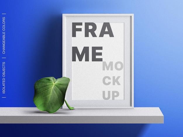 Maqueta interior de la lona del cartel de la foto del marco en el estante con la hoja tropical aislada