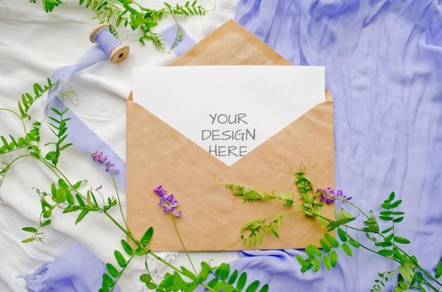 Maqueta de invitación de boda con flores y cintas de seda.