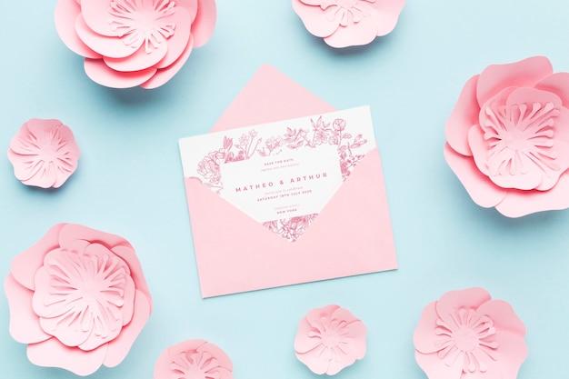 Maqueta de invitación de boda con flores de papel sobre fondo azul.