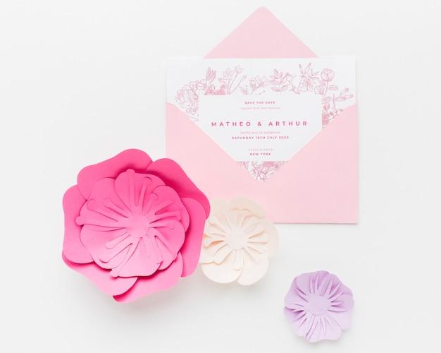 Maqueta de invitación de boda con flores de papel sobre fondo blanco.