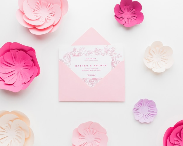 Maqueta de invitación de boda con flores de papel sobre fondo blanco