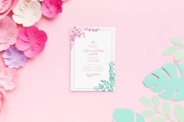 Maqueta de invitación de boda con flores de papel sobre fondo rosa