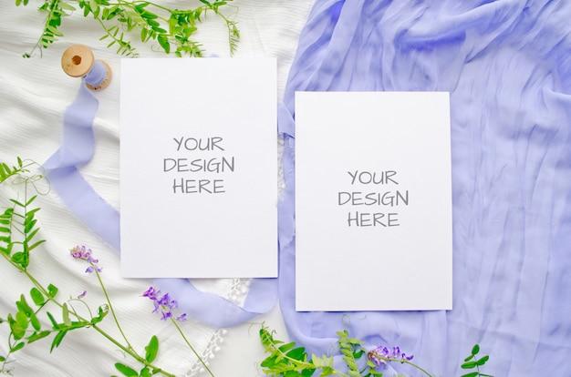 Maqueta de invitación de boda con flores violetas y delicadas cintas de seda sobre un fondo blanco.