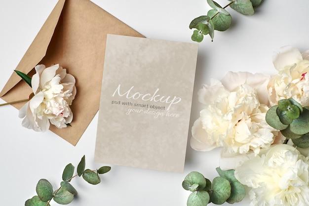 Maqueta de invitación de boda o tarjeta de felicitación con sobre y flores de peonía blanca con ramitas de eucalipto