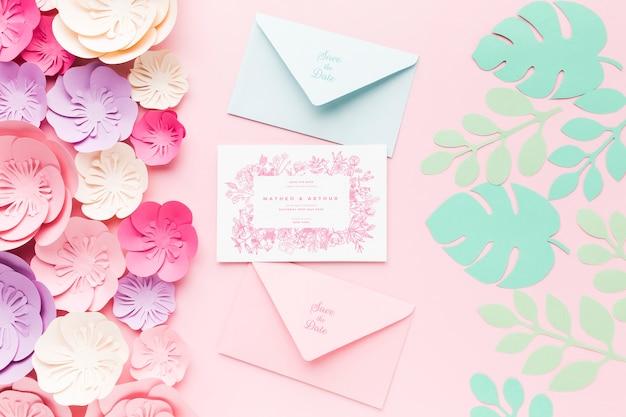 Maqueta de invitación de boda y sobres con flores de papel sobre fondo rosa