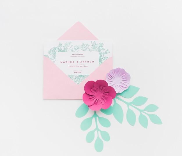 Maqueta de invitación con flores de papel sobre fondo blanco.