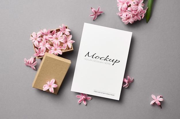Maqueta de invitación o tarjeta de felicitación con flores de primavera rosa en caja