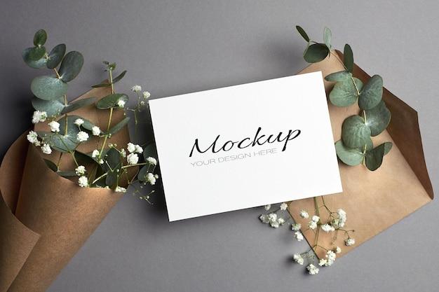 Maqueta de invitación o tarjeta de felicitación con sobre y flores de eucalipto e hipsophila
