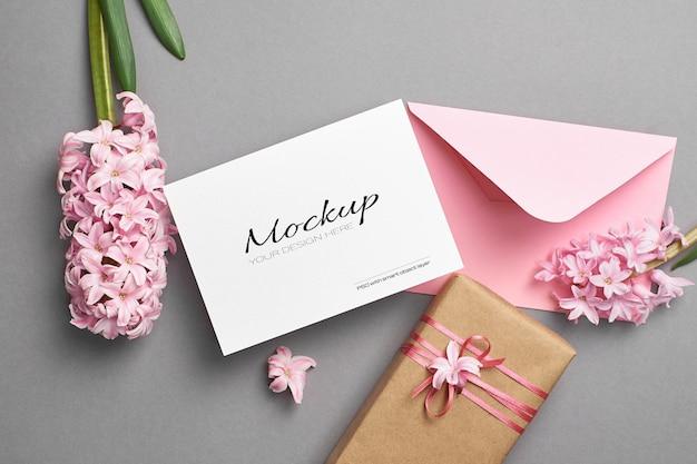 Maqueta de invitación o tarjeta de felicitación con sobre rosa, caja de regalo y flores de jacinto