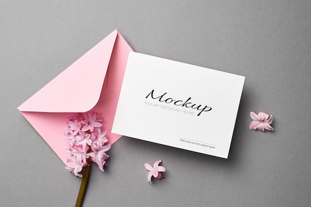 Maqueta de invitación o tarjeta de felicitación con sobre rosa y flores