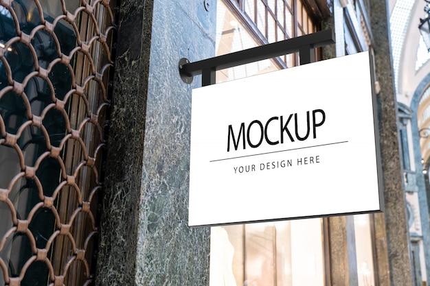 Maqueta de letrero cuadrado blanco para el logotipo de la tienda en la calle