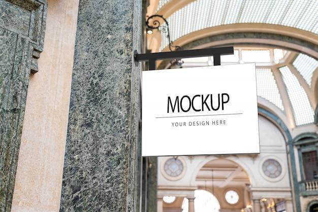 Maqueta de letrero de logotipo cuadrado blanco sobre mármol en una galería de lujo