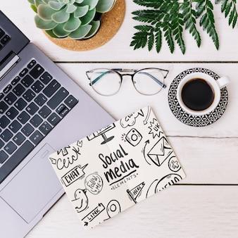 Maqueta de libreta con café y portátil
