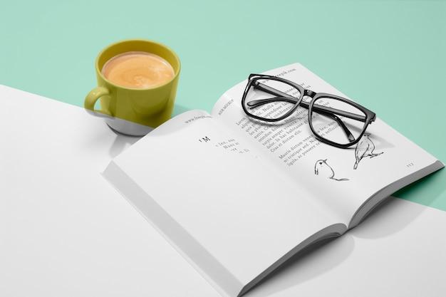 Maqueta de libro abierto de alto ángulo con café y vasos