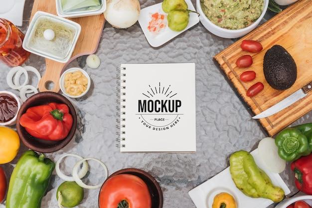 Maqueta de libro de recetas rodeado de comida sana