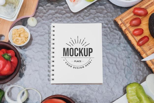 Maqueta de libro de recetas rodeado de verduras