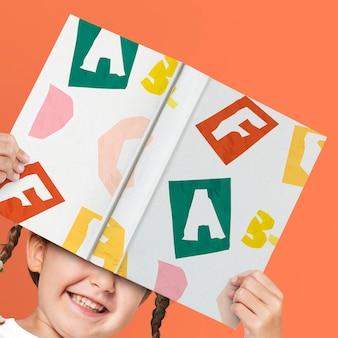 Maqueta de libro de tapa dura en manos de niña