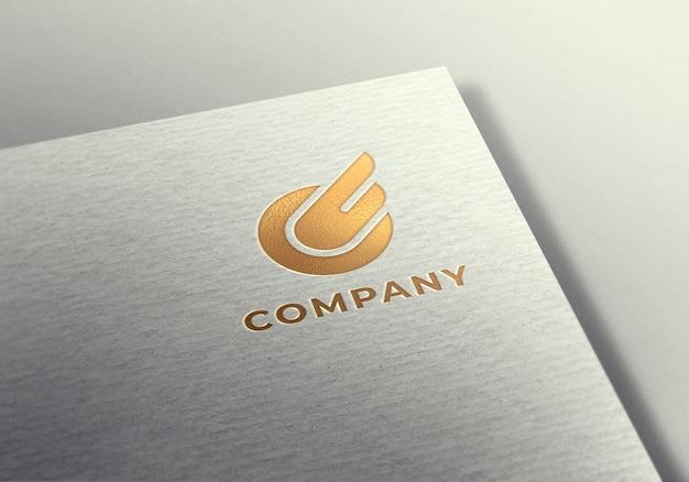 Maqueta de logo dorado sobre papel blanco con textura
