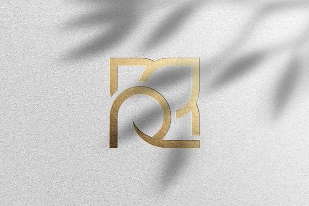 Maqueta de logo dorado sobre papel blanco