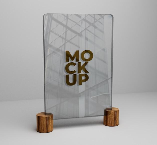 Maqueta de logo dorado sobre vidrio sobre fondo de madera