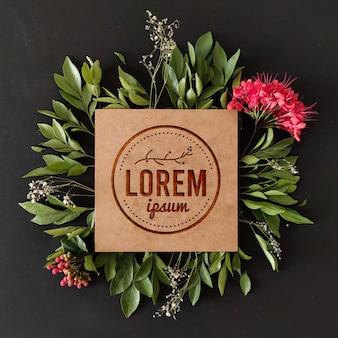 Maqueta con logo floral grabado en madera con marco natural