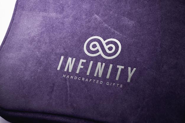 Maqueta con logo plateado en una caja de tela morada