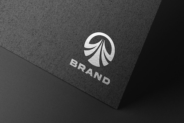 Maqueta de logo plateado en relieve sobre papel negro