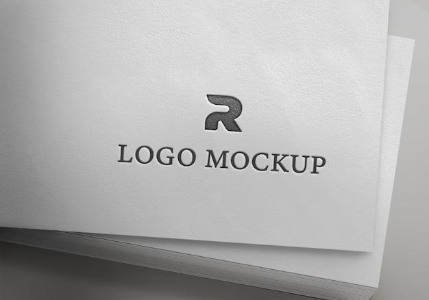 Maqueta con logo plateado sobre papel