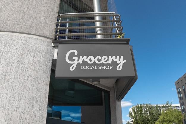 Maqueta de logotipo blanco en señalización rectangular gris que cuelga en la fachada del edificio