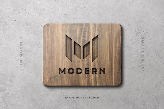 Maqueta de logotipo de cartel de madera en muro de hormigón