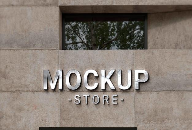 Maqueta de logotipo corporativo en fachada de hormigón