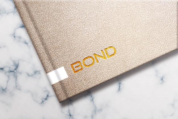 Maqueta de logotipo dorado en diseño de cuaderno de cuero
