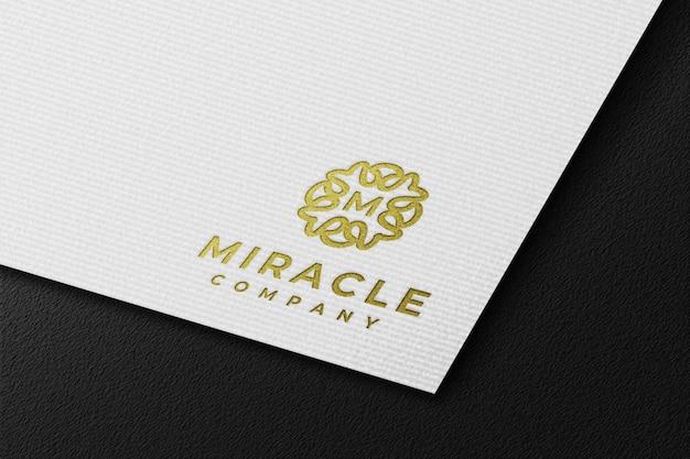 Maqueta de logotipo dorado de lujo limpio en papel prensado blanco