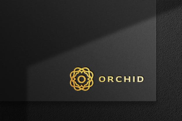 Maqueta de logotipo dorado de lujo limpio en papel prensado negro con sombra