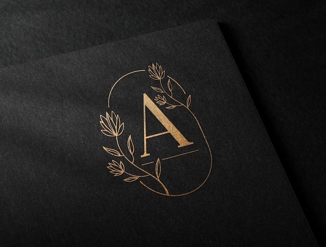 maqueta de logotipo dorado de lujo en papel artesanal negro