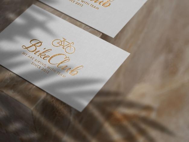 Maqueta de logotipo dorado en relieve sobre papel de lino