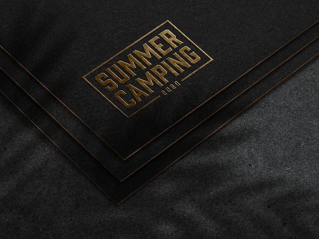 Maqueta de logotipo dorado en relieve sobre papel oscuro