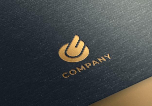 Maqueta de logotipo dorado sobre papel negro con textura