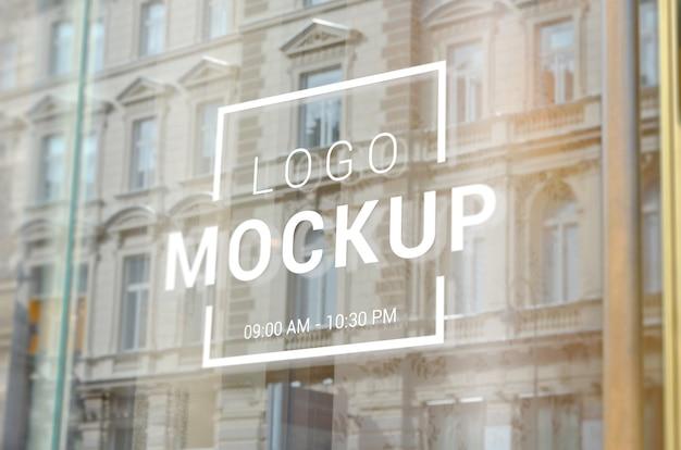 Maqueta de logotipo de escaparate de tienda de la ciudad. reflexión de edificios de la ciudad sobre vidrio.
