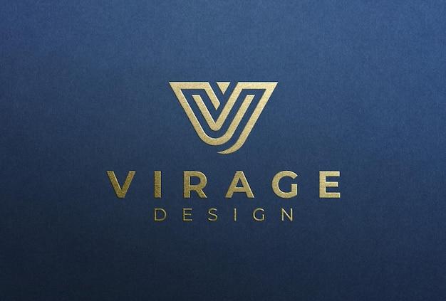 Maqueta de logotipo estampado con estampado de logotipo dorado en papel azul profundo
