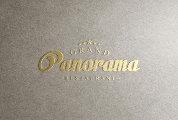 Maqueta de logotipo de lámina dorada en relieve sobre papel artesanal gris