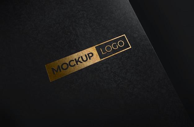 Maqueta de logotipo de lámina de oro con fondo de papel negro