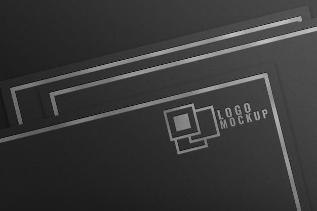 Maqueta de logotipo de lámina de plata sobre papel negro