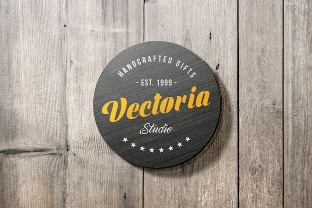 Maqueta de logotipo de letrero metálico en pared de madera