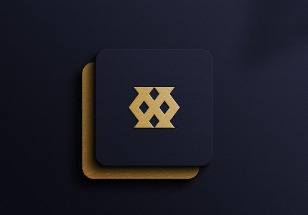 Maqueta de logotipo de lujo con lámina dorada sobre fondo azul oscuro