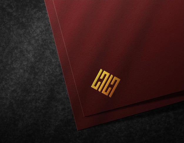 Maqueta de logotipo de lujo papel oscuro y efecto de relieve dorado