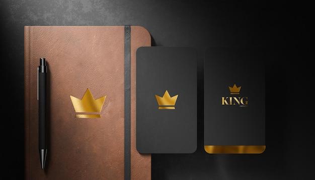 Maqueta de logotipo de lujo en tarjeta de visita y diario de cuero sobre fondo negro