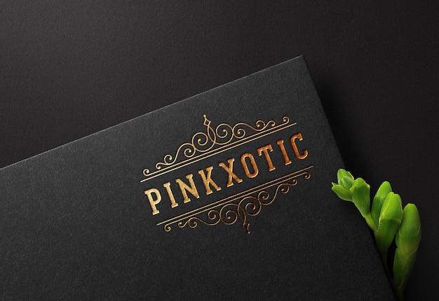 Maqueta de logotipo en papel negro con efecto estampado dorado prensado
