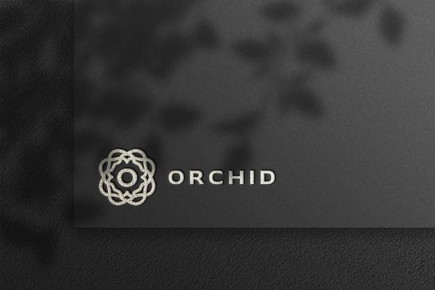 Maqueta de logotipo plateado de lujo en papel artesanal negro con sombra